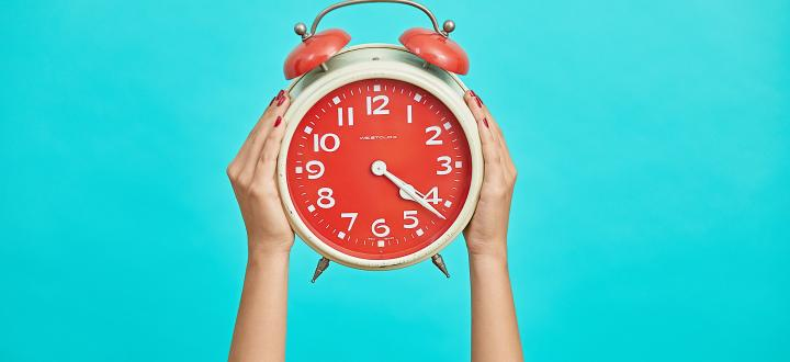 Photo of a red alarm clock being held by two hands on a cyan background