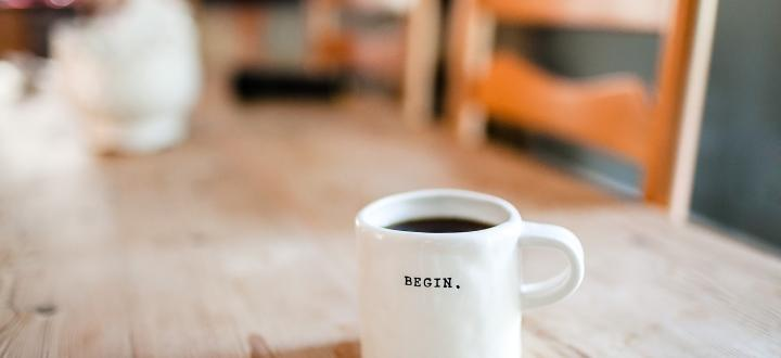 Photo of a white coffee mug on a table with the word 'begin' written on it