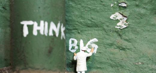 Photo of small figure painting 'think big' onto a green pipe and wall