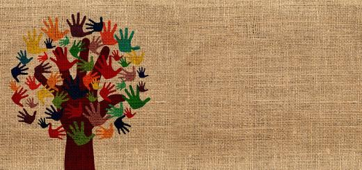 Painting of a tree with leaves of multiple colour handprints on a hessian canvas background