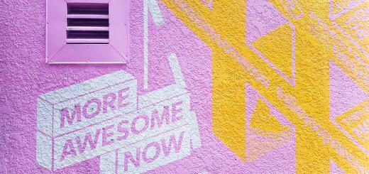 A wall painted bright pink and yellow with 'more awesome now' stencilled on a white background in pink paint