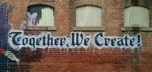 A wall with 'Together We Create' painted on it in gothic style lettering