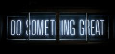Neon sign saying 'Do something great' on a dark background